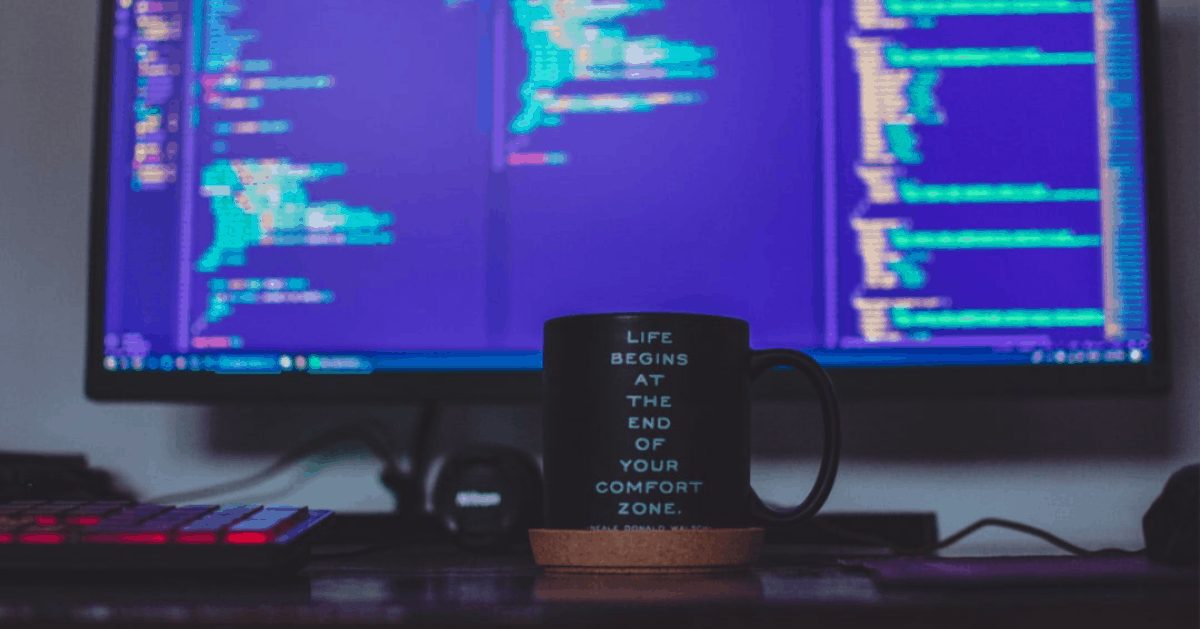 A Coffee Cup In Front Of A Computer With Ruby On Rails And Javascript Code