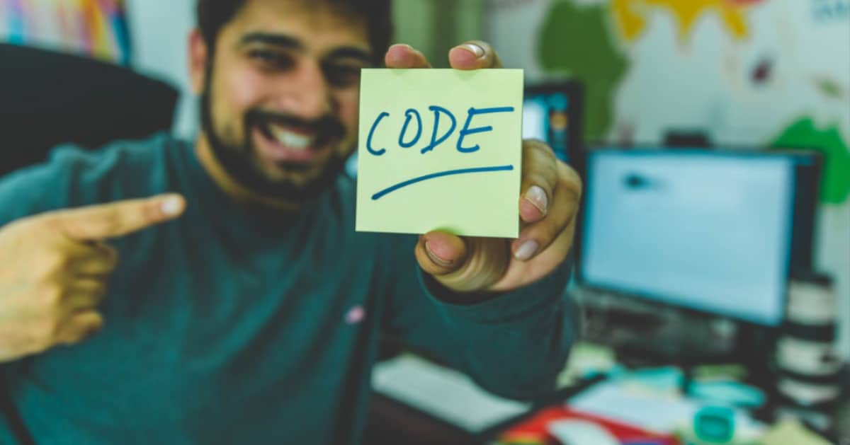 a web developer at a computer holding a sticky note that says code on it
