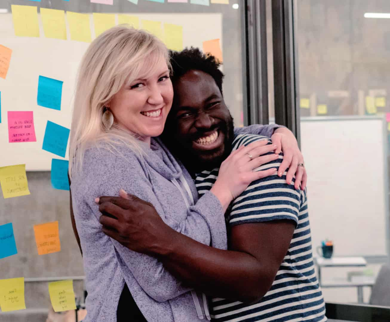 Two Diverse Coding Students Hugging Inside A Coding Bootcamp
